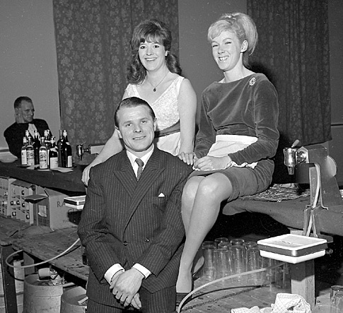 February 1966: The landlord of the Fountain Inn, Morley, and two of his barmaids at a function at Morley Town Hall.